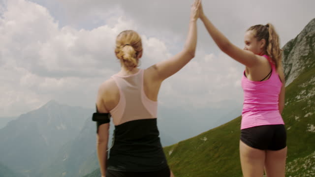 SLO MO Ecstatic women on the top of a mountain