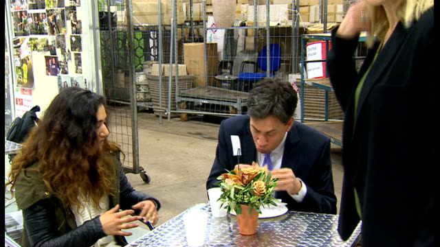 ed miliband launches new welfare policy lib / tx photography** ed miliband eating bacon sandwich during visit to flower market end lib - ed miliband stock-videos und b-roll-filmmaterial