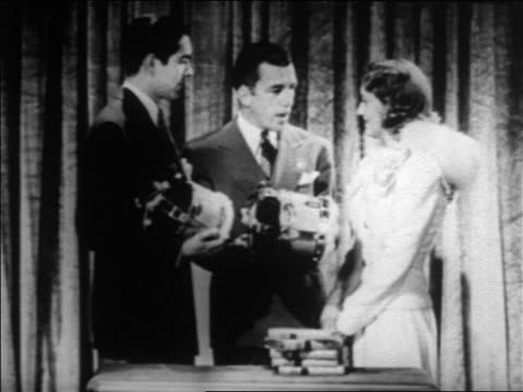 vídeos y material grabado en eventos de stock de ed sullivan giving award to jeanette macdonald as tyrone power looks on / newsreel - mujer con grupo de hombres