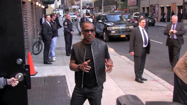 eddie murphy poses for photographers as he arrives at the 'late show with david letterman' in new york 10/25/11 - eddie murphy stock videos & royalty-free footage
