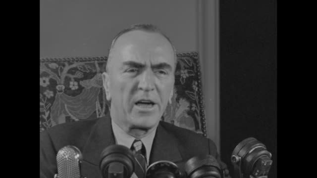 cu eddie rickenbacker wwi fighter ace and congressional medal of honor winner sitting at desk speaking to camera with microphones in front sot he... - エディ リッケンバッカー点の映像素材/bロール