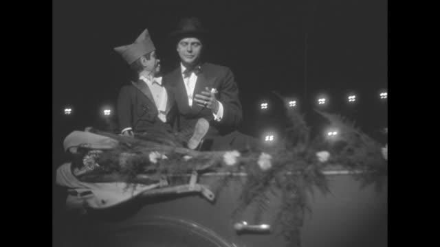 vidéos et rushes de edgar bergen and charlie mccarthy ride on an open convertible in a nighttime parade - ventriloque