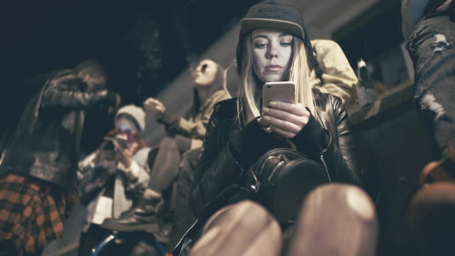 vídeos y material grabado en eventos de stock de edgy woman with mobile phone hanging out with friends at night and singing - social media