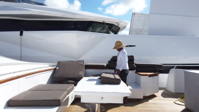 vídeos y material grabado en eventos de stock de edher nandi places cushions on the deck of miss penny 5 a mangusta yacht as he helps prepare it for display at the 60th annual fort lauderdale... - cojín