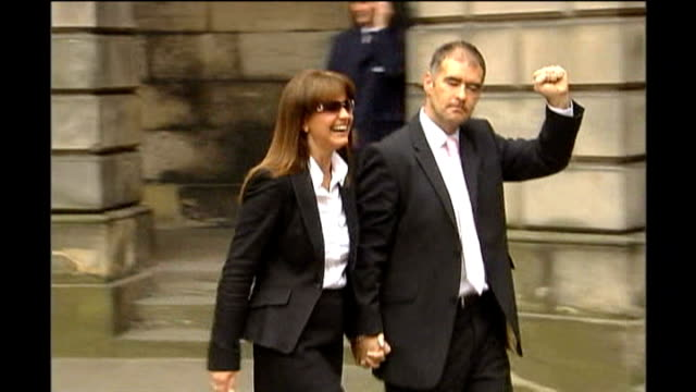 edinburgh: edinburgh court of session: slow motion seq tommy sheridan out of court shaking his fist with wife gail sheridan following libel case... - news of the world stock videos & royalty-free footage