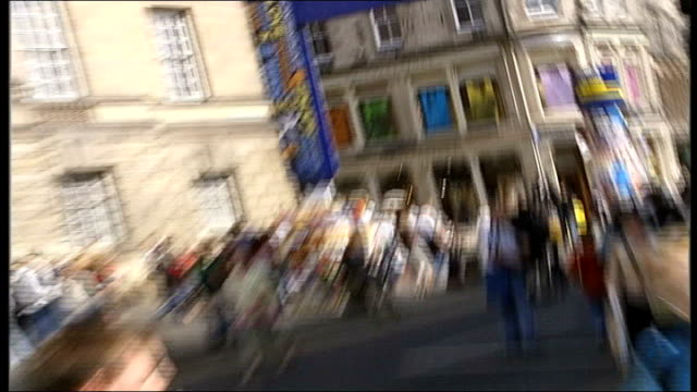 edinburgh ext sign above road ' edinburgh fringe' pull out to man sitting on pavement playing saxaphone mime artist performing on busy pavement - woodwind instrument stock videos and b-roll footage