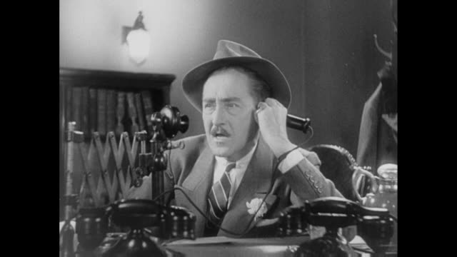 1931 editor (adolph menjou) and reporter (pat o'brien) quip over phone, impatient to share and hear news - 1931 stock videos & royalty-free footage