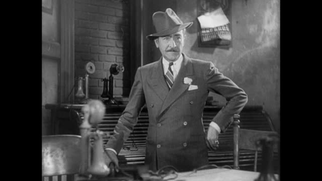 1931 editor (adolph menjou) asks reporter (pat o'brien) to help him move roll top desk containing escaped convict - roll over stock videos and b-roll footage