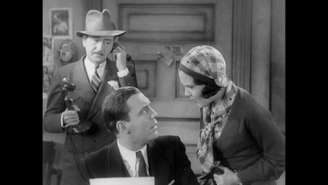 1931 editor (adolph menjou) on phone and reporter (pat o'brien) make it clear to woman (mary brian) that she is not wanted as they work frantically on their exclusive - choice stock-videos und b-roll-filmmaterial