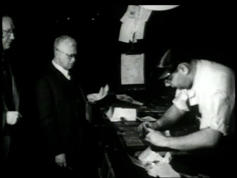 1948 MONTAGE Editors supervising as compositor puts final newspaper story into slots / New York City, New York, United States