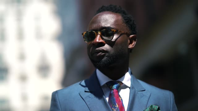 Edmond Kamara from the blog Cuts For Him wears sunglasses a blue suit blazer jacket a watch brown leather shoes a white shirt a blue and pink tie...