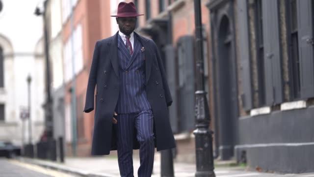 Edmond Kamara wears a burgundy hat a long coat a blue striped blazer jacket suit pants brown leather pants a white shirt a tie during London Fashion...