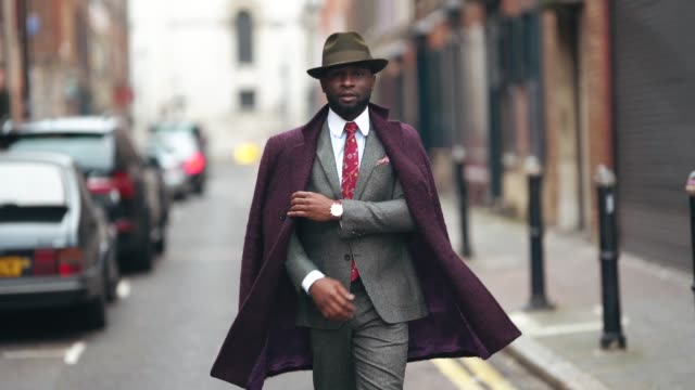 edmond kamara wears a green hat, a purple coat, a gray suit with blazer jacket, a white shirt, red tie, during london fashion week men's january 2019... - gray jacket stock videos & royalty-free footage