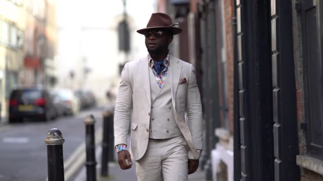 stockvideo's en b-roll-footage met edmond kamara wears a hat a white three pieces suit a scarf white blazer jacket white pants white sneakers shoes sunglasses during london fashion... - sportschoen