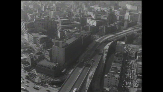 edobashi local traffic moves on city streets beneath the tokyo metropolitan expressway construction project. - 1960~1969年点の映像素材/bロール
