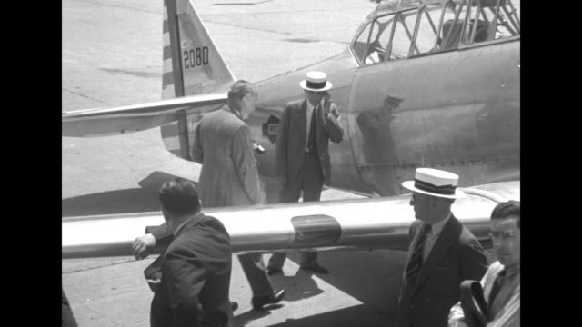 edsel and henry ford examine components of a curtiss p-40 airplane as management officials and us army air corps personnel watch / the airplane is... - ヘンリー・フォード点の映像素材/bロール