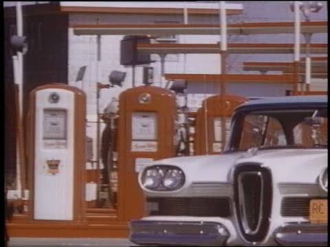 1958 pan edsel driving toward camera past row of gas pumps at gas station - 1958 stock videos & royalty-free footage