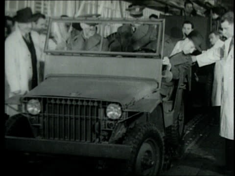 edsel ford drives first military scout cars to come out of automotive plant / detroit michigan united states - ジープ点の映像素材/bロール