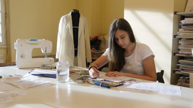 vídeos y material grabado en eventos de stock de educación. clase de arte. estudiantes de moda dibujo de modas de las mujeres. - estudio de diseño