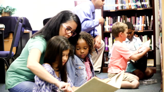education. brarian reads book to elementary students in library or classroom. - storytelling stock videos & royalty-free footage