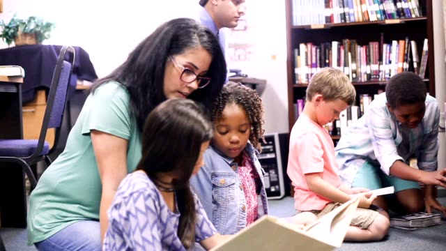 vídeos de stock e filmes b-roll de education. brarian reads book to elementary students in library or classroom. - voluntário