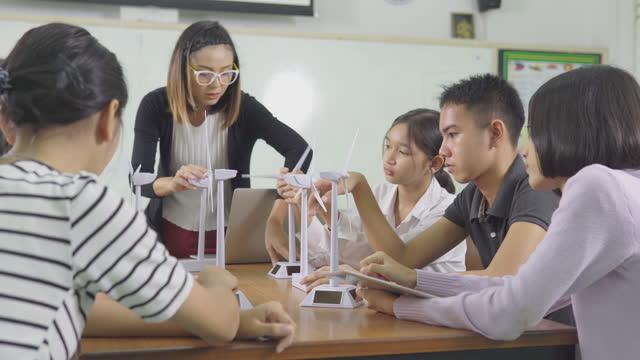 concetto di istruzione. l'insegnante spiega con interesse il funzionamento della turbina eolica ai bambini. - modello dimostrativo video stock e b–roll