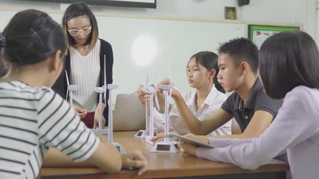 education concept.the teacher explains the operation of the wind turbine to the children with interest. - elementary school building stock videos & royalty-free footage