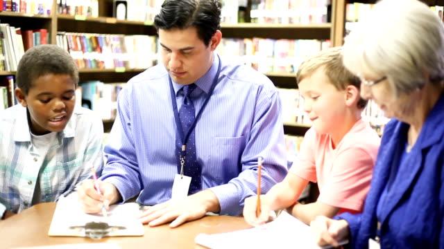 Bildung - Grundschule Ratgeber mit Studenten in der Bibliothek.
