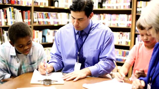 教育-小學輔導員與學生在圖書館。 - 少於10秒 個影片檔及 b 捲影像