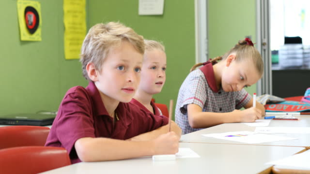 education of primary school students answering questions in class - uniform stock videos & royalty-free footage