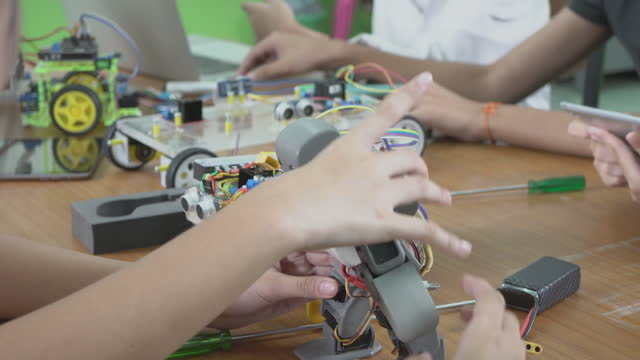 education topics :smart school boy building a small robot arm and uses laptop to program software for robotics engineering class as a school science project.science and people concept. - skill stock videos & royalty-free footage