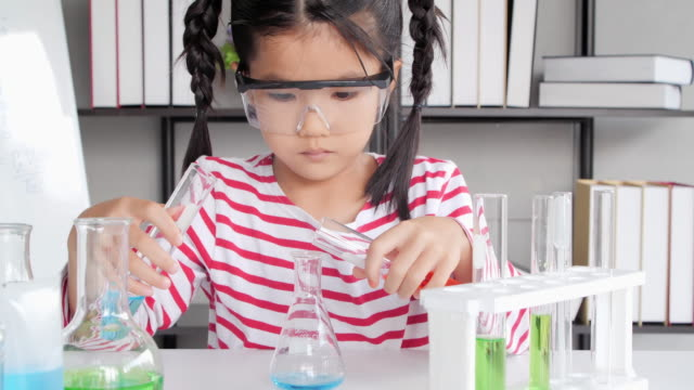 education topics:funny little girl doing experiments in the laboratory.science and education. - becher video stock e b–roll