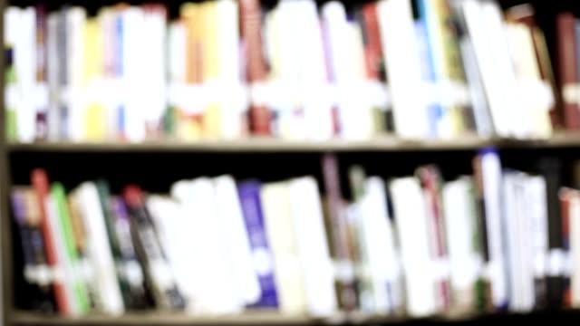 stockvideo's en b-roll-footage met onderwijs-defocused bibliotheek boekenplanken vol met boeken. - boekwinkel