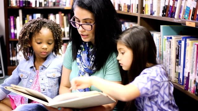 education.librarian reads book to elementary students in library or classroom. - elementary age stock videos & royalty-free footage