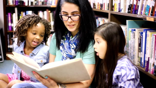 education.librarian reads book to elementary students in library or classroom. - picture book stock videos and b-roll footage