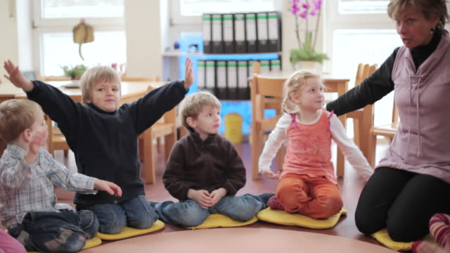 vídeos y material grabado en eventos de stock de ms educator and children sitting in circle on floor and they making finger play / potsdam, brandenburg, germany - escuela preescolar