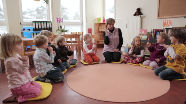 WS Educator and children sitting in circle on round carpet / Potsdam, Brandenburg, Germany