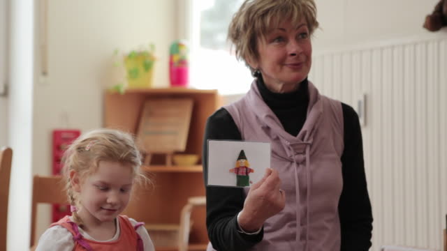 ms educator showing picture to children / potsdam, brandenburg, germany - nursery school building stock videos & royalty-free footage