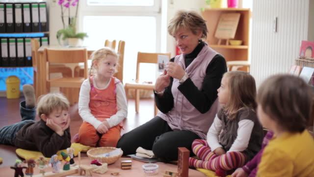 vídeos de stock e filmes b-roll de ms educator showing picture to children / potsdam, brandenburg, germany - edifício de infantário