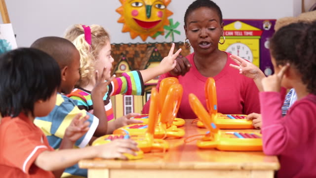 ms pan educator teaching children how to count using computers in daycare / richmond, virginia, usa - barnomsorg bildbanksvideor och videomaterial från bakom kulisserna