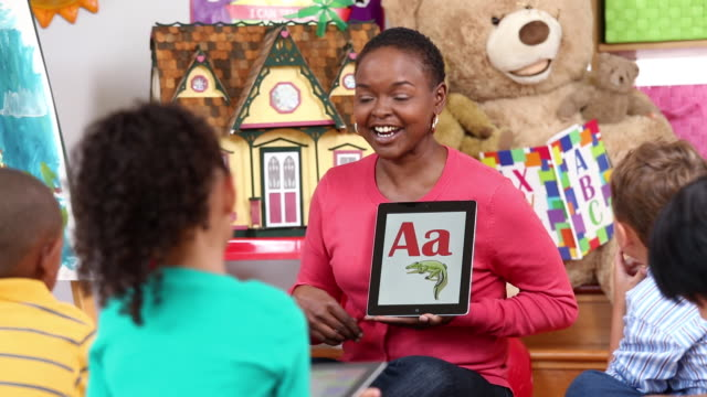 MS PAN Educator Teaching Children the Alphabet on Tablet Computers in Daycare / Richmond, Virginia, USA