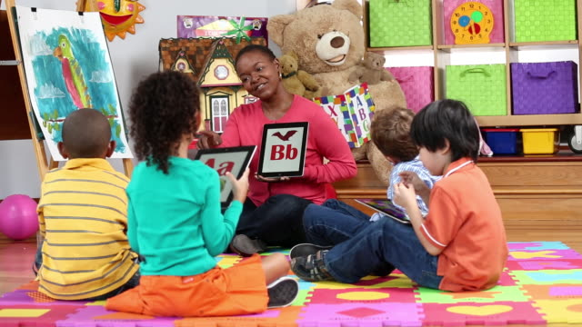 ws pan educator teaching children the alphabet on tablet computers in daycare / richmond, virginia, usa - barnomsorg bildbanksvideor och videomaterial från bakom kulisserna
