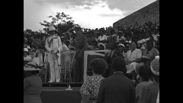 edward, duke of windsor and governor of the bahamas, stands on platform surrounded by bahamian people, with the duchess of windsor seated at his... - エドワード8世点の映像素材/bロール