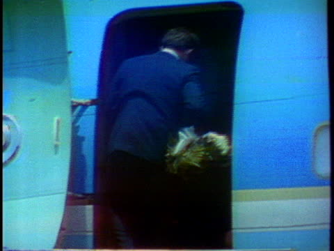 edward m. kennedy picks up a flower spray that fell off the coffin of senator robert f. kennedy's coffin and takes it into the airplane. - brother点の映像素材/bロール
