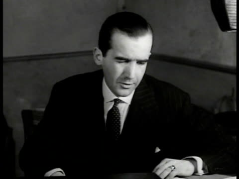 Edward R Murrow at desk 'Hello America from London more German planes over coast of Britain' EXT London streets in smoke amp ruins Bombed bus burning...