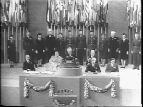 Edward Stettinius at podium with flags behind him introduces President Harry Truman / United Nations Delegates in crowd stand to applaud the...