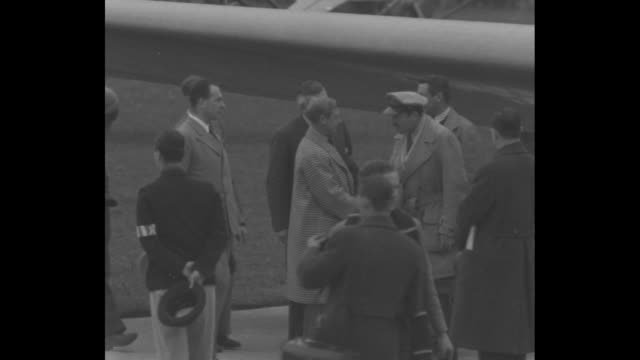 stockvideo's en b-roll-footage met edward walks across mildenhall airport tarmac with officials / he shakes hands with pilots in front of wing of airplane / front view of airplane with... - start  en landingsbaan