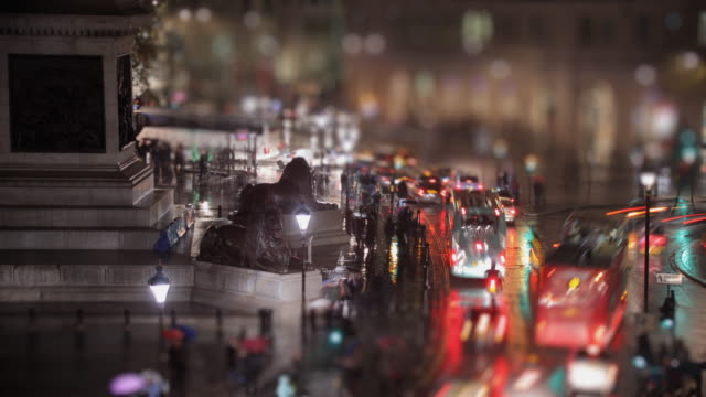 T/L WS SELECTIVE FOCUS Edwin Landseer's Lions guarding Nelson's Column and traffic on Trafalgar Square at rainy night / London, England