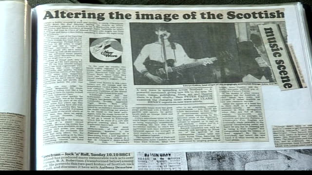 edwyn collins releases new album after lifethreatening illness hands turning pages of scrapbook of old press cuttings as music heard sot - アルバムのタイトル点の映像素材/bロール