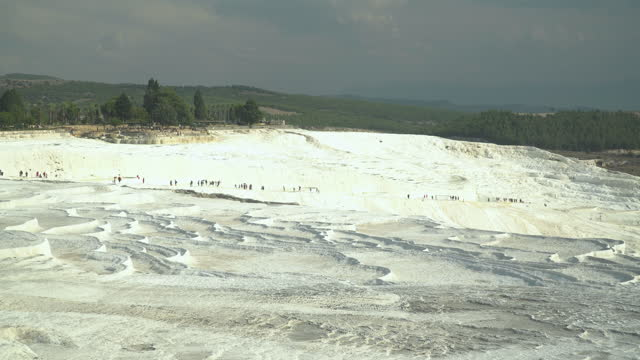 effect of climate change, traveler walking to pamukkale pools without flowing water, droughts, in summer.  layers of travertines form terraces of carbonate minerals in pamukkale, a natural landmark of natural phenomenon, on sunset in southwest turkey. - natural landmark stock videos & royalty-free footage